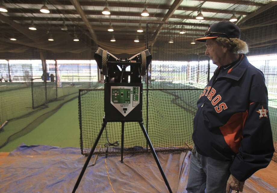 Astros minor league equipment manager Paul Burgess stands near the computerized pitching machine inside of the batting cages at the club's spring training facility. Photo: Karen Warren, Houston Chronicle