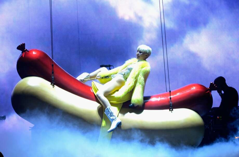 "Miley Cyrus rides a hot dog during her ""Bangerz"" tour at Rogers Arena on February 14, 2014 in Vancouver, Canada. Photo: Kevin Mazur, WireImage"