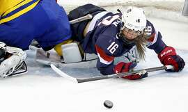 Kelli Stack (16) collides with Sweden goalie Valentina Wallner (35) in the first period at the Winter Olympics in Sochi, Russia, Monday, Feb. 17, 2014. The USA defeated Sweden 6-1. (Carlos Gonzalez/Minneapolis Star Tribune/MCT)