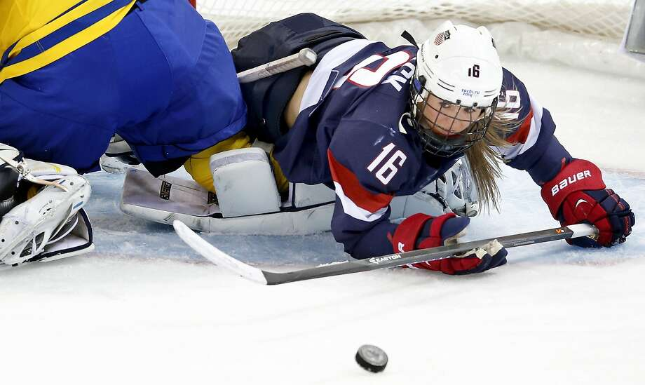 Kelli Stack (16) collides with Sweden goalie Valentina Wallner in the first period of Team USA's 6-1 victory. Photo: Carlos Gonzalez, McClatchy-Tribune News Service