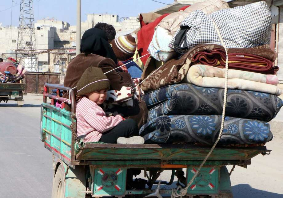 Syrians sit on a cart loaded with belongings as they leave for a safer area in the Hanano district of the northern Syrian city of Aleppo. Photo: Fadi Al-Halabi / AFP / Getty Images / AFP
