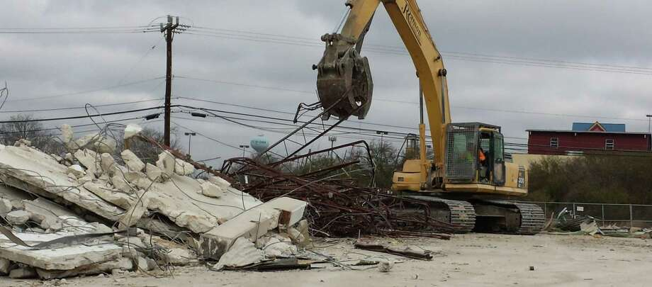 A crane moves large pieces of metal and concrete Jan. 31 as workers clear debris of the former Live Oak Civic Center on Pat Booker Road. Photo: Jeff B. Flinn / NE Herald
