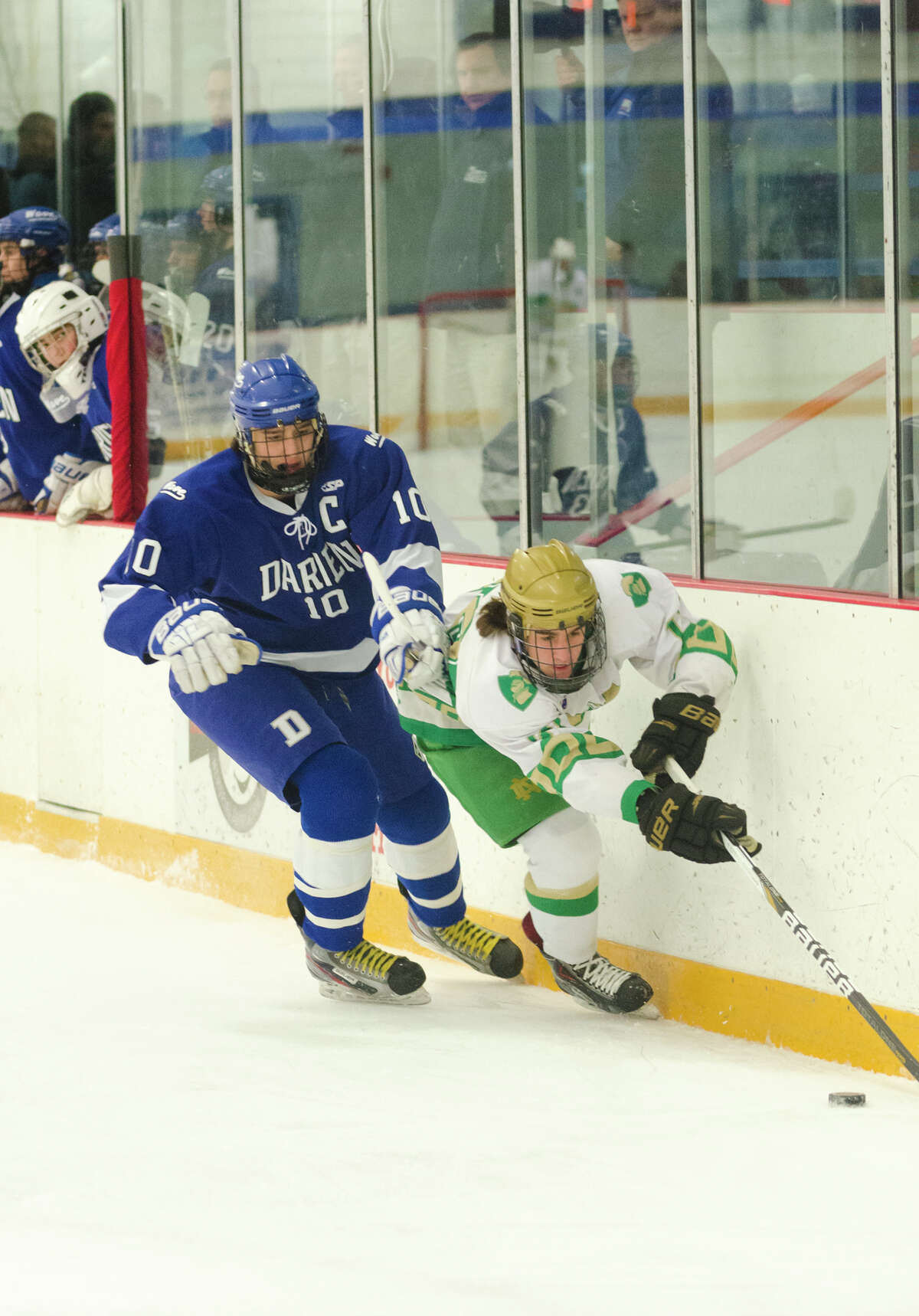 Notre Dame West Haven's Kyle Lynch (20) and Darien's Jack Massie (10) battle for control of the puck during the boys ice hockey game at Bennett Skating Rink in West Haven on Monday, Feb. 17, 2014.