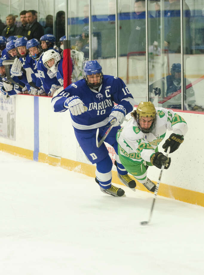 Notre Dame West Haven's Kyle Lynch (20) becomes airborne as Darien's Jack Massie (10) battles for control of the puck during the boys ice hockey game at Bennett Skating Rink in West Haven on Monday, Feb. 17, 2014. Photo: Amy Mortensen / Connecticut Post Freelance