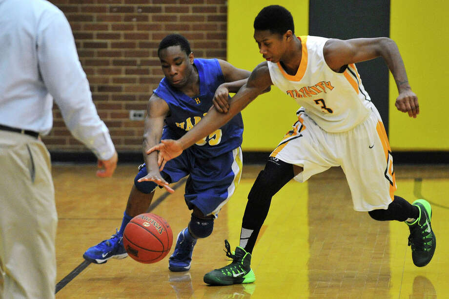 Trinity Catholic's Tremaine Fraiser attempts to steal the ball from Harding's Ramir Johnson during their game at Trinity Catholic High School in Stamford, Conn., on Monday, Feb. 27, 2014. Trinity Catholic won, 78-62. Photo: Jason Rearick / Stamford Advocate