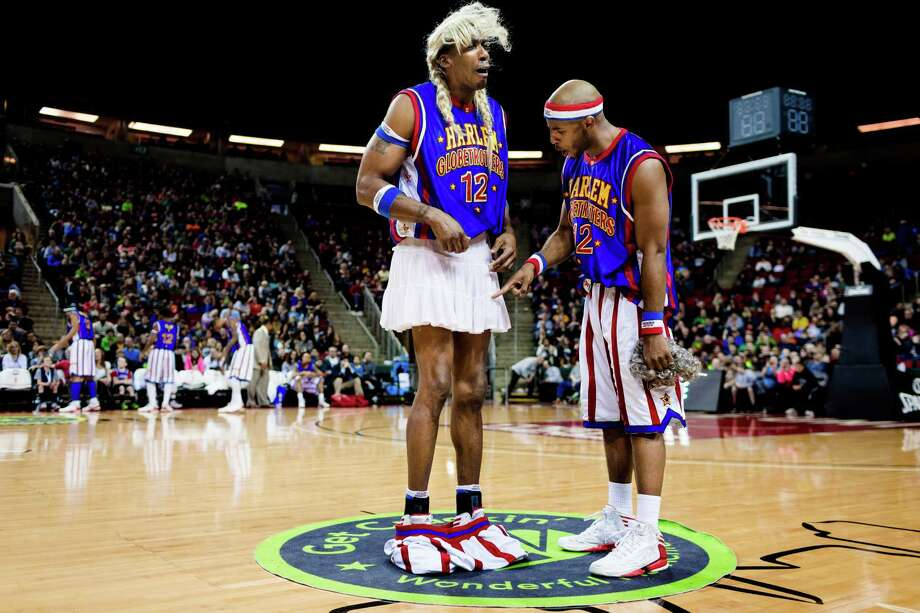 "After ""pants-ing"" an opposing player, Harlem Globetrotters Hi-Lite, center, feigns sadness as Dizzy, right, points at a skirt revealed under Hi-Lite's shorts during the ""Fans Rule"" World Tour Monday, Feb. 17, 2014, at KeyArena in Seattle. The kid-friendly Globetrotters have thrilled families and millions of fans for 88 years. Photo: JORDAN STEAD, SEATTLEPI.COM / SEATTLEPI.COM"