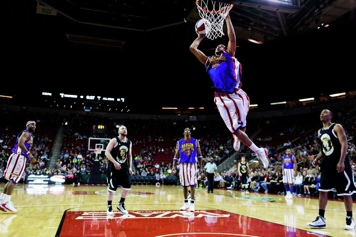 The Harlem Globetrotters slam dunk on the hardwood during their