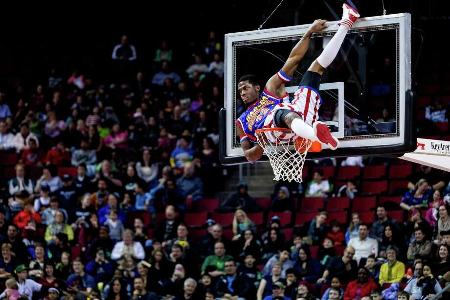 "Harlem Globetrotters player Flip clambers to the top of the basket mid-game during the ""Fans Rule"" World Tour Monday, Feb. 17, 2014, at KeyArena in Seattle. The kid-friendly Globetrotters have thrilled families and millions of fans for 88 years. Photo: JORDAN STEAD, SEATTLEPI.COM / SEATTLEPI.COM"