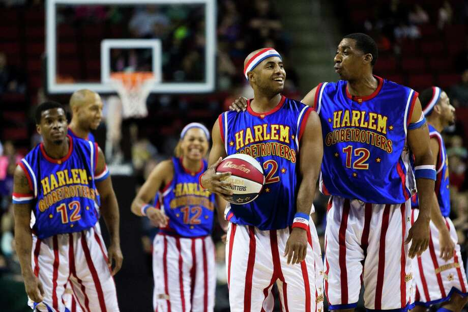 "Hi-Lite, right, laughs with Dizzy, center right, both of the Harlem Globetrotters, during the ""Fans Rule"" World Tour Monday, Feb. 17, 2014, at KeyArena in Seattle. The kid-friendly Globetrotters have thrilled families and millions of fans for 88 years. Photo: JORDAN STEAD, SEATTLEPI.COM / SEATTLEPI.COM"