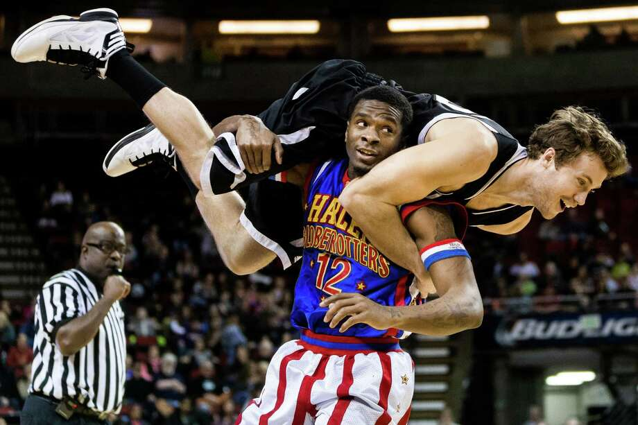 "Harlem Globetrotters player Flip, bottom, tosses an opponent over his shoulder during gameplay at the ""Fans Rule"" World Tour Monday, Feb. 17, 2014, at KeyArena in Seattle. The kid-friendly Globetrotters have thrilled families and millions of fans for 88 years. Photo: JORDAN STEAD, SEATTLEPI.COM / SEATTLEPI.COM"