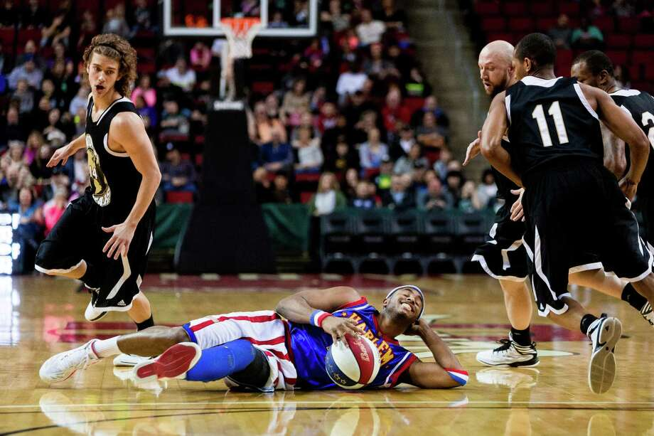 "Posted at the top of the key, Harlem Globetrotters player Dizzy kicks himself around in a circle while dribbling the ball as opposing players circle him during the ""Fans Rule"" World Tour Monday, Feb. 17, 2014, at KeyArena in Seattle. The kid-friendly Globetrotters have thrilled families and millions of fans for 88 years. Photo: JORDAN STEAD, SEATTLEPI.COM / SEATTLEPI.COM"