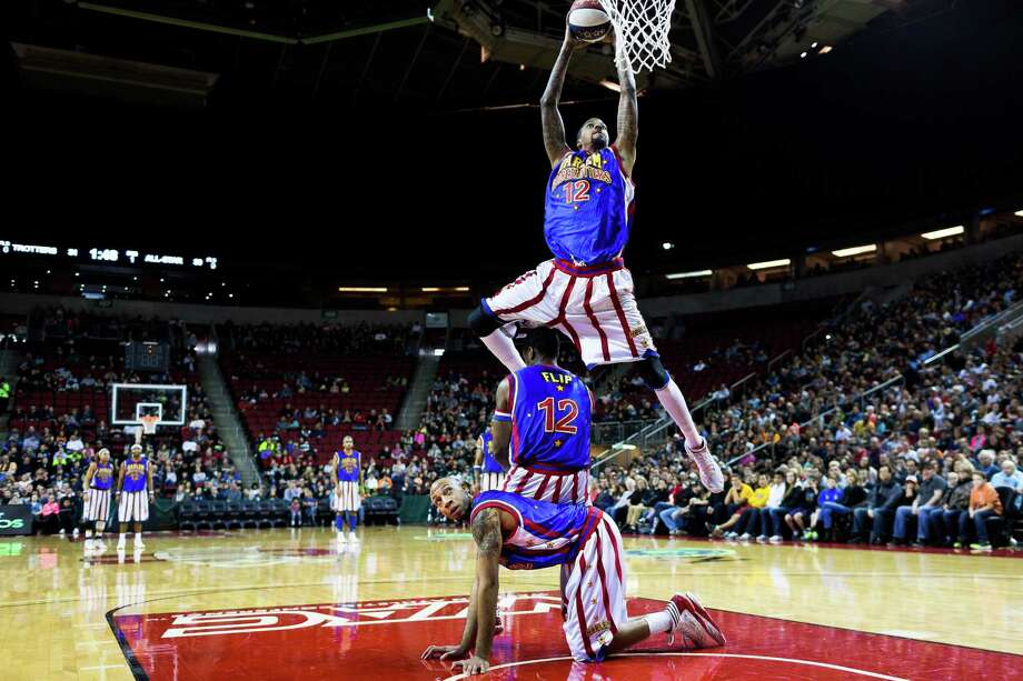 "A Harlem Globetrotter slam dunks over a pile of other players on the hardwood during their ""Fans Rule"" World Tour Monday, Feb. 17, 2014, at KeyArena in Seattle. The kid-friendly Globetrotters have thrilled families and millions of fans for 88 years. Photo: JORDAN STEAD, SEATTLEPI.COM / SEATTLEPI.COM"