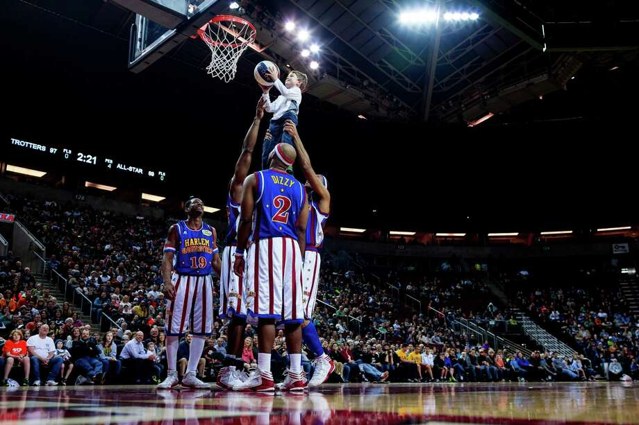 "Harlem Globetrotters hoist up a young fan to make a basket during their ""Fans Rule"" World Tour Monday, Feb. 17, 2014, at KeyArena in Seattle. The kid-friendly Globetrotters have thrilled families and millions of fans for 88 years. Photo: JORDAN STEAD, SEATTLEPI.COM / SEATTLEPI.COM"