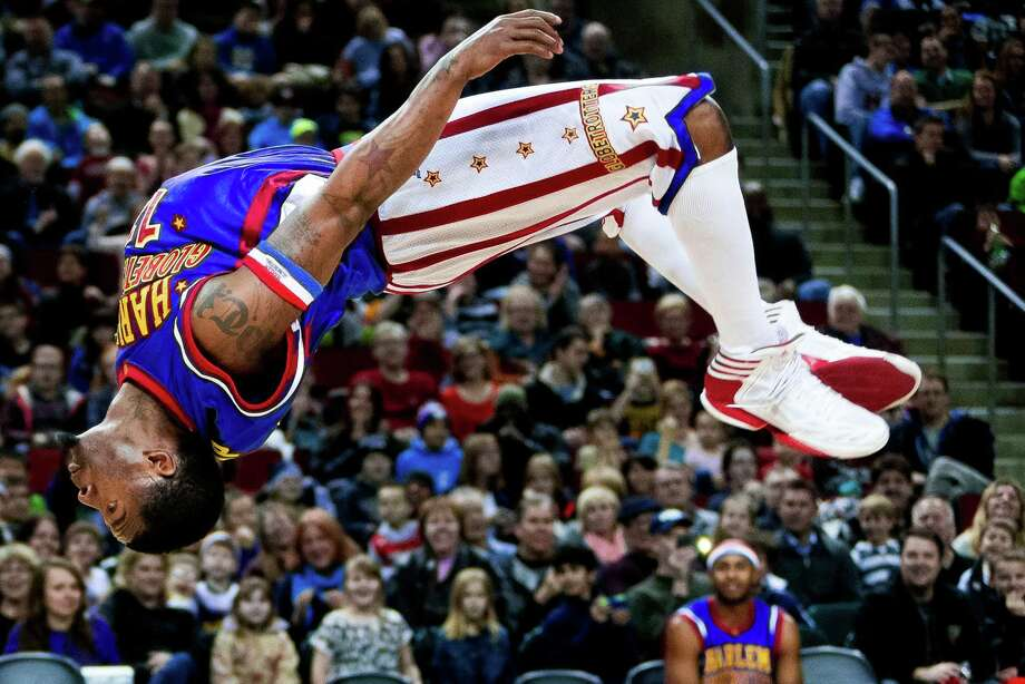 "Harlem Globetrotters player Flip remains true to his name during the ""Fans Rule"" World Tour Monday, Feb. 17, 2014, at KeyArena in Seattle. The kid-friendly Globetrotters have thrilled families and millions of fans for 88 years. Photo: JORDAN STEAD, SEATTLEPI.COM / SEATTLEPI.COM"