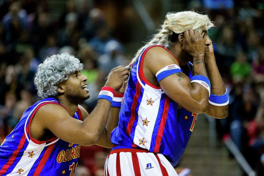 "Hi-Lite, right, and Dizzy, left, both of the Harlem Globetrotters, don wigs and sneak up on an opponent shooting free throws during the ""Fans Rule"" World Tour Monday, Feb. 17, 2014, at KeyArena in Seattle. The kid-friendly Globetrotters have thrilled families and millions of fans for 88 years. Photo: JORDAN STEAD, SEATTLEPI.COM / SEATTLEPI.COM"