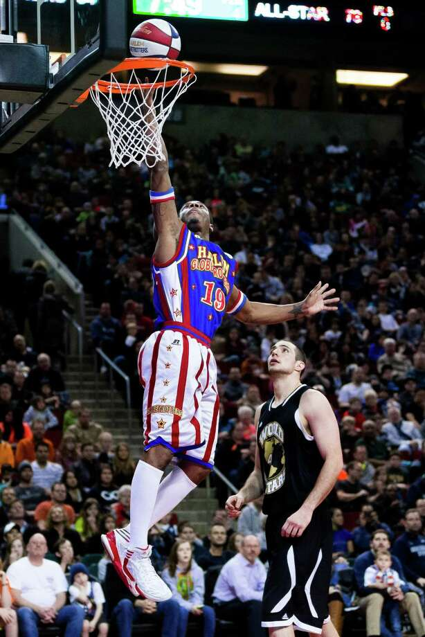 """Flip takes it to the basket during the """"Fans Rule"""" World Tour Monday, Feb. 17, 2014, at KeyArena in Seattle. The kid-friendly Globetrotters have thrilled families and millions of fans for 88 years. Photo: JORDAN STEAD, SEATTLEPI.COM / SEATTLEPI.COM"""