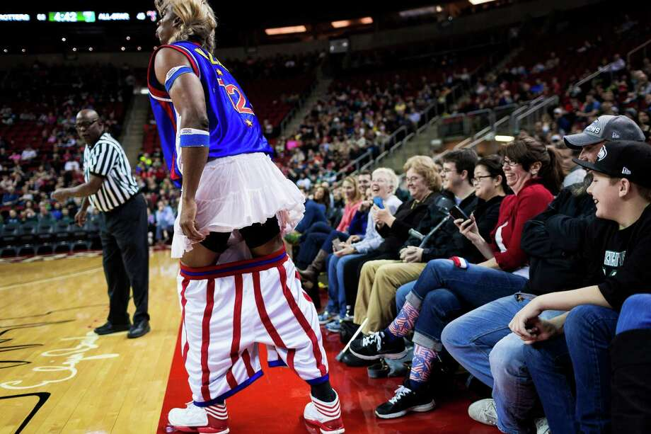 "After ""pants-ing"" an opposing player, Harlem Globetrotters player Hi-Lite, left, shows off a skirt revealed under his shorts during the ""Fans Rule"" World Tour Monday, Feb. 17, 2014, at KeyArena in Seattle. The kid-friendly Globetrotters have thrilled families and millions of fans for 88 years. Photo: JORDAN STEAD, SEATTLEPI.COM / SEATTLEPI.COM"