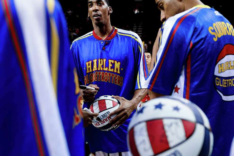 "The Harlem Globetrotters sign autographs following their ""Fans Rule"" World Tour Monday, Feb. 17, 2014, at KeyArena in Seattle. The kid-friendly Globetrotters have thrilled families and millions of fans for 88 years. Photo: JORDAN STEAD, SEATTLEPI.COM / SEATTLEPI.COM"