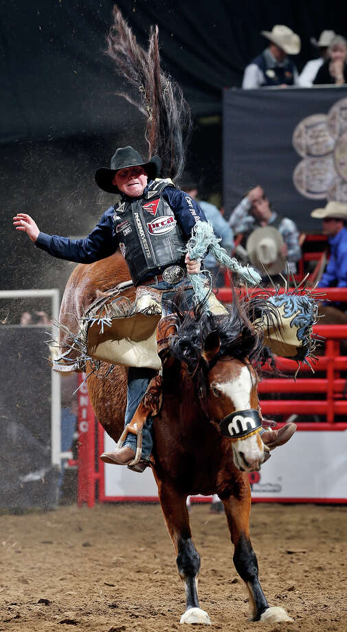 Taos Muncy, of Corona, NM, competes in the saddle bronc  riding event during the San Antonio Stock Show & Rodeo Monday Feb. 17, 2014 at the AT&T Center. Muncy scored an 83 on the ride. Photo: Edward A. Ornelas, San Antonio Express-News / © 2014 San Antonio Express-News