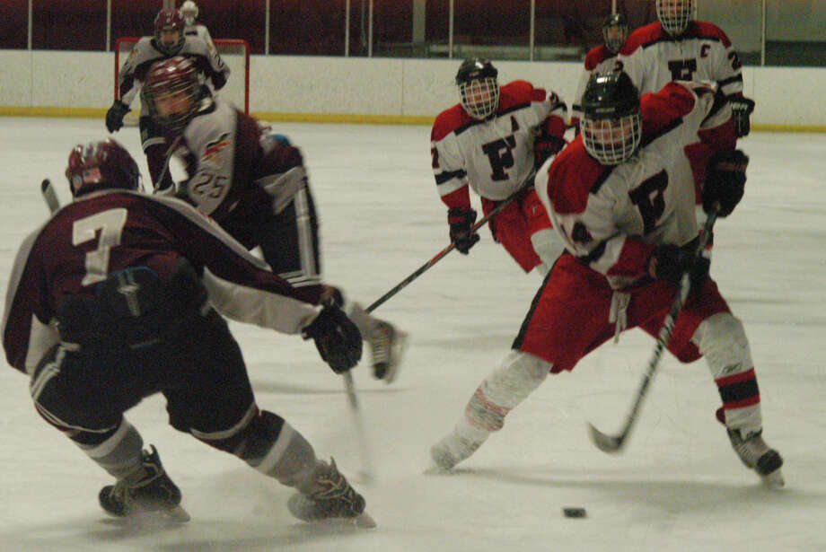 Fairfield co-op's Austin Armas, right, on the puck against the Milford co-op on Monday, Feb. 17 in a non-conference boys hockey game at Wonderland Of Ice in Bridgeport. Milford won 1-0. Photo: Andy Hutchison / Fairfield Citizen