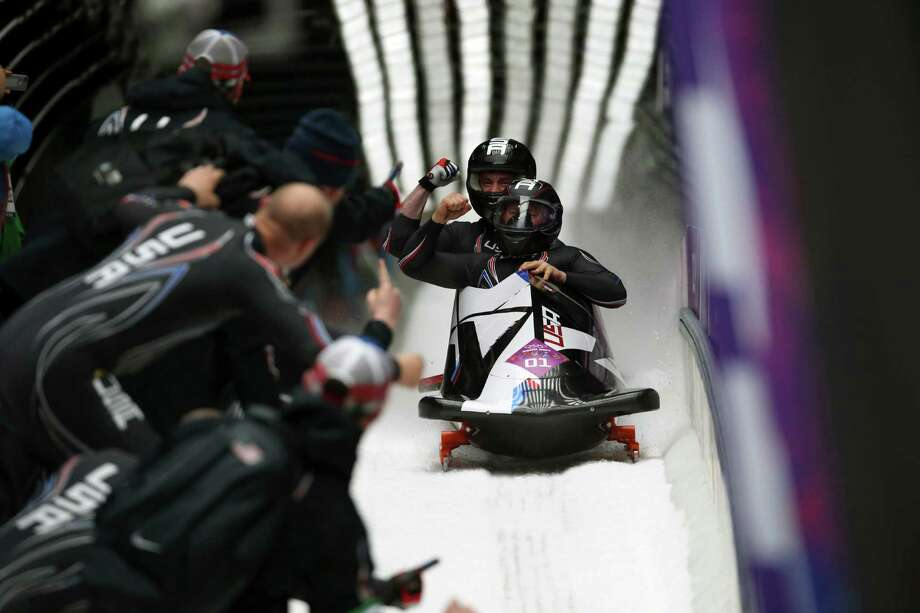 Steven Holcomb and Steven Langton of the U.S. celebrate with coaches after their bronze medal run in the two-man bobsled event at the Sanki Sliding Center during the 2014 Winter Olympics in Krasnaya Polyana, Russia, Feb. 17, 2014. (Josh Haner/The New York TImes)  ORG XMIT: XNYT41 Photo: JOSH HANER / NYTNS
