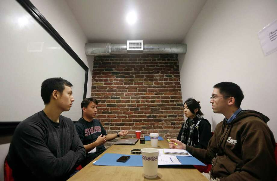 Ian Wong, from left, Willy Chu, Yuriko Tamura and Steve Nguyen meet during a coding and team formation session at the FinCapDev San Francisco Hackathon. Photo: Jeff Chiu, STF / AP