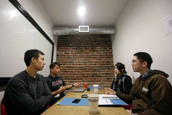 Ian Wong, from left, Willy Chu, Yuriko Tamura and Steve Nguyen meet during a coding and team formation session at the FinCapDev San Francisco Hackathon.