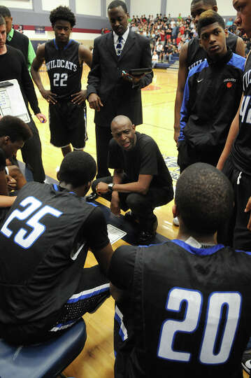 Dekaney head coach Chris Wilson, center, pumps up his team during a 4th guarter timeout against The