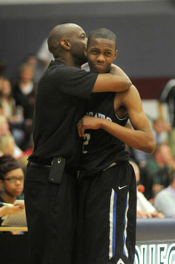 Dekaney senior guard Joseph Kilgore, right, gets a hug from his coach, Chris Wilson, during the wani