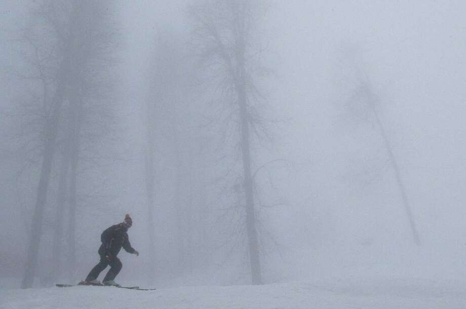 A skier tries to navigate through dense fog near the alpine training slopes in Krasnaya Polyana, Russia. Photo: Christophe Ena / Associated Press / AP