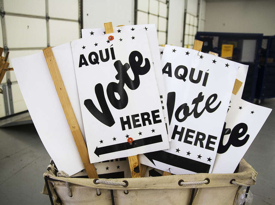 Voting signs in storage at the Bexar County Elections Warehouse could show up today at one of the 32 voting places across the county. Polls open at 8 a.m. today for 11 days of early voting. Photo: Alma E. Hernandez / For The San Antonio Express-News