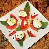 """Caprese (kah-PRAY-say): A fresh, uncooked salad of tomatoes, mozzarella, basil, seasonings and olive oil. Audio: Click here to hear the term """"Caprese."""""""