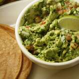 """Guacamole (wock-a-MOH-leh): A dip of mashed avocados, lemon or lime juice, and optional ingredients such as onions, tomatoes, chiles and other spices. Audio: Click here to hear the term """"Guacamole."""""""