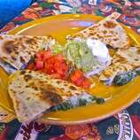 """Quesadilla (keh-sah-DEE-yah): Don't pull a Napolean Dynamite and pronounce a hard L for this dish of two flour tortillas grilled and filled with melted cheese and other items. Audio: Click here to hear the term """"Quesadilla."""""""