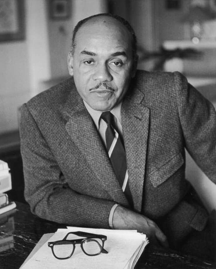 Ralph Ellison (1914 - 1994) wearing a tweed jacket and striped tie, sitting at a table with his horn-rimmed eyeglasses resting on a manuscript. Photo: Bernard Gotfryd, Getty Images / Premium Archive