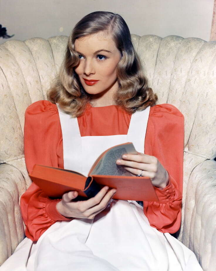 Veronica Lake (1922-1973), US actress, wearing a red blouse beneath a white apron dress, sitting in an armchair as she reads a book, circa 1955. Photo: Silver Screen Collection, Getty Images / 2011 Silver Screen Collection