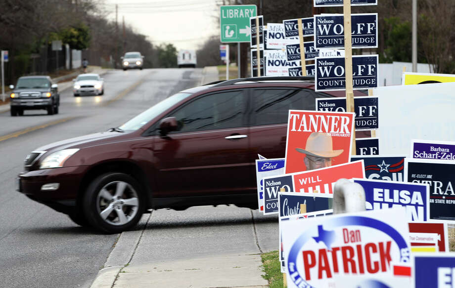 Traffic passes by election signs Tuesday morning February 18, 2014 at the Brook Hollow Branch of the San Antonio Public Library on the first day of early voting for the March 4 primaries. Photo: JOHN DAVENPORT, SAN ANTONIO EXPRESS-NEWS / ©San Antonio Express-News/Photo may be sold to the public