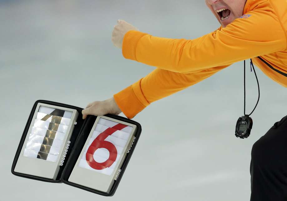 A coach displays the lap time to Bob de Jong of the Netherlands as he competes in the men's 10,000-meter speedskating race at the Adler Arena Skating Center during the 2014 Winter Olympics in Sochi, Russia, Tuesday, Feb. 18, 2014. Photo: Matt Dunham, Associated Press