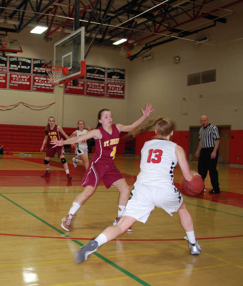 New Canaan High School's Elizabeth Miller (#13) looks to drive past St. Joseph's Tess Lockwood (#4) in a girls basketball contest in New Canaan Conn. on Monday, Feb. 17, 2014. Photo: Dave Crandall / New Canaan News freelance
