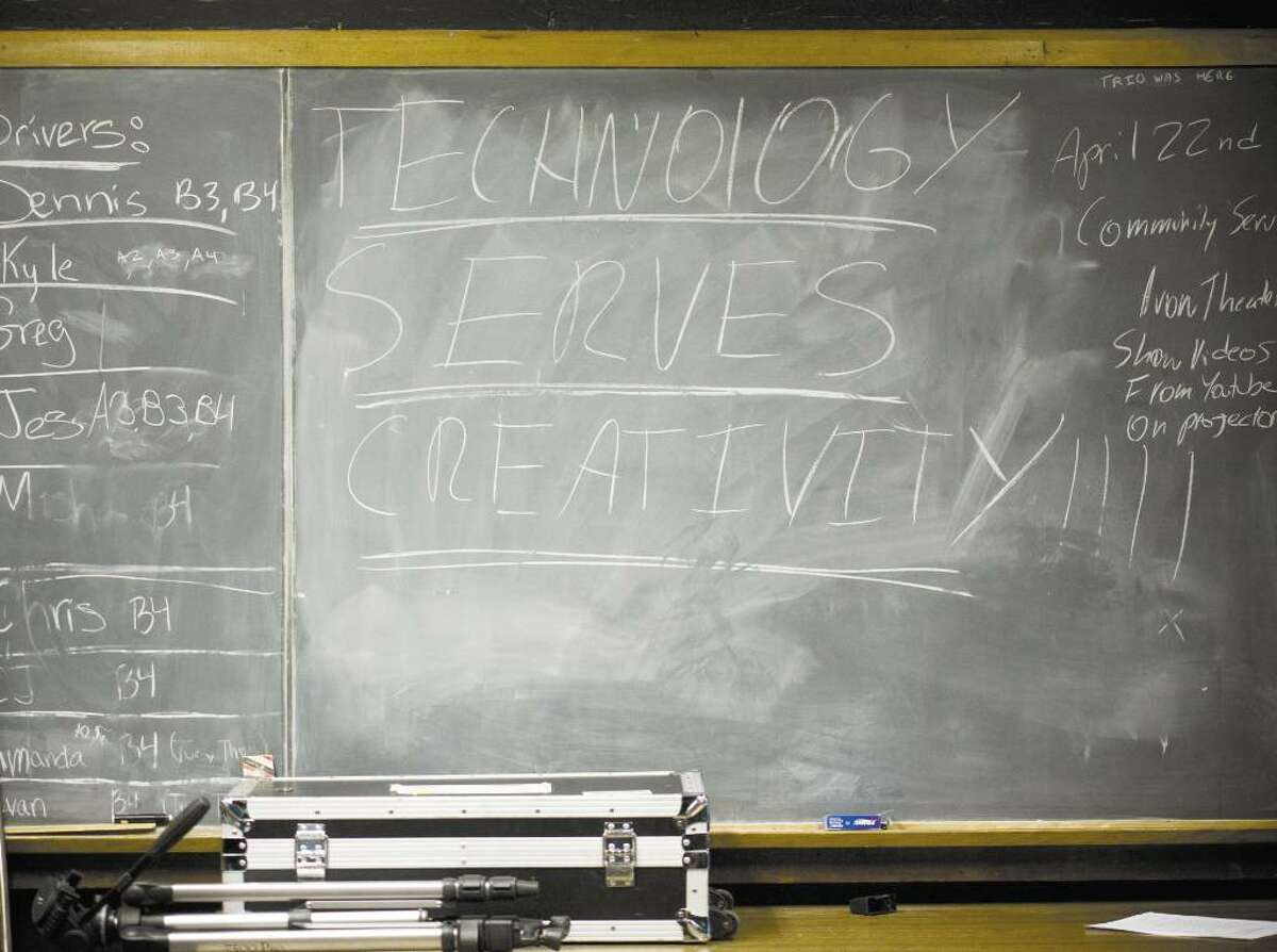 """A chalkboard on the wall in the studio of the Media Technology class at AITE reads """"Technology serves creativitity."""""""