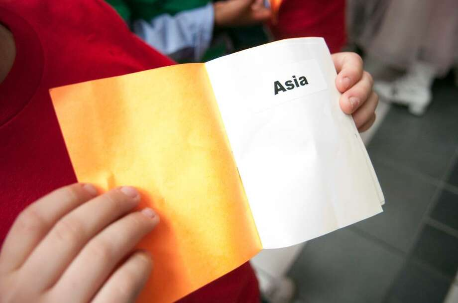 """A student holds up a """"passport"""" that would be stamped at various activity booths during the Junior First Lego League Expo at the Academy of Information Technology & Engineering in Stamford, Conn. on Sunday, Feb. 7, 2010. Photo: Chris Preovolos / Stamford Advocate"""