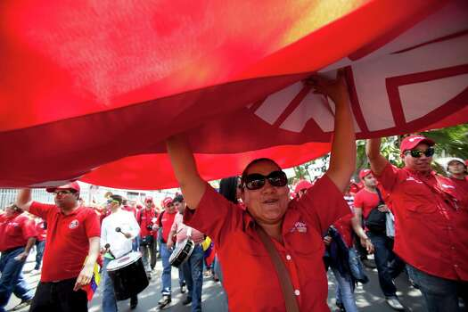 Employees of Petroleos de Venezuela, PDVSA, work together to hold up their red banner as they walk during a pro-government march in Caracas, Venezuela, Tuesday, Feb. 18, 2014. The Venezuelan government accuses the Obama administration of siding with student protesters it has blamed for violence that led to three deaths last week. Maduro claims the U.S. is trying to stir up unrest to regain dominance of South America's largest oil producer. Photo: Alejandro Cegarra, AP / AP