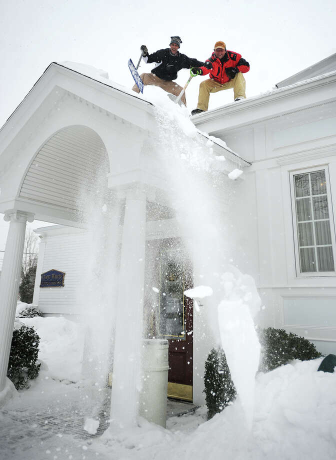Neil Dougherty, left, and Chris Kuba, both of Milford, clear accumulated snow from the roof of Cody White funeral home on Broad Street on The Green in Milford, Conn on Tuesday, February 18, 2014. Photo: Brian A. Pounds / Connecticut Post