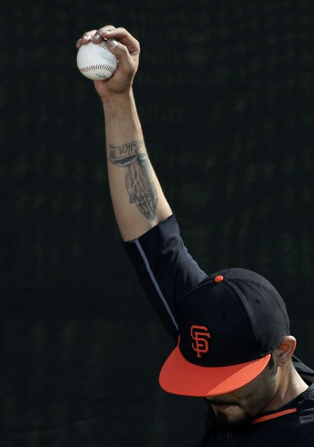 San Francisco Giants relief pitcher Sergio Romo warms up to throw during spring training baseball practice on Sunday, Feb. 16, 2014, in Scottsdale, Ariz. Photo: Gregory Bull, Associated Press
