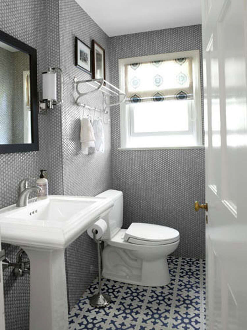After: Gorgeous Gray The homeowner steered clear of major plumbing work by keeping the room's layout the same. Moroccan cement floor tiles, from Artesana Interiors, almost read like a fine rug. Ditching the sponge-painted effect for Nemo's penny tiles delivered the biggest impact space-wise. The homeowner also swapped out the dated vanity for a classic Kohler pedestal sink; an efficient commode by Toto replaced the old water-wasting toilet. A custom medicine cabinet hangs in the powder room, along with a towel rack from Moon River Chattel. Read: Peek inside a restored Victorian cottage in Arkansas