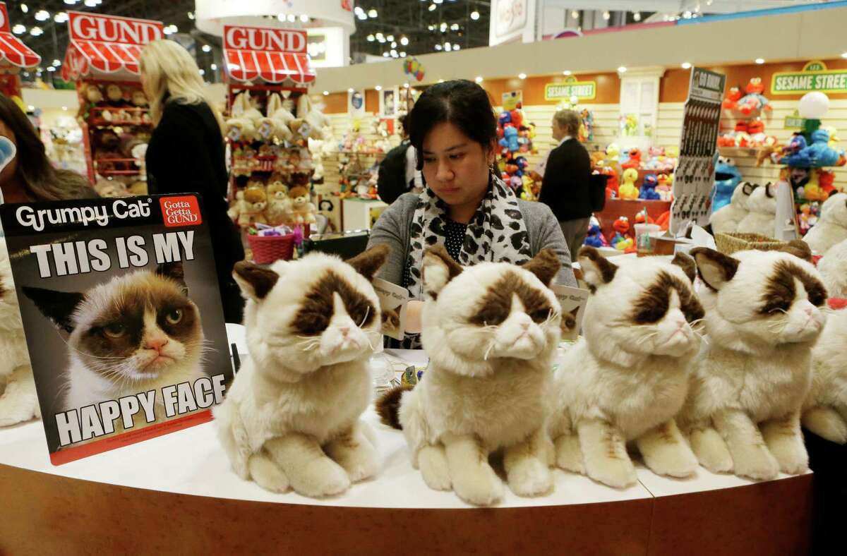 People pass a Grumpy the Cat display by Gund as they attend Toy Fair 2014 at the Jacob K. Javits Convention Center Sunday, Feb. 16, 2014, in New York. The 111th American International Toy Fair opened in New York Sunday. (AP Photo)