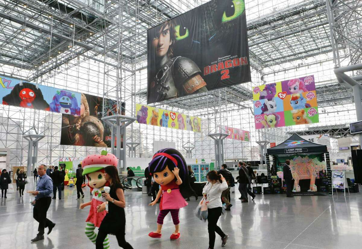 Strawberry Shortcake, left, and Cherry Jam, center, walk among people arriving at Toy Fair 2014 at the Jacob K. Javits Convention Center Sunday, Feb. 16, 2014, in New York. The 111th American International Toy Fair opened in New York Sunday. (AP Photo)