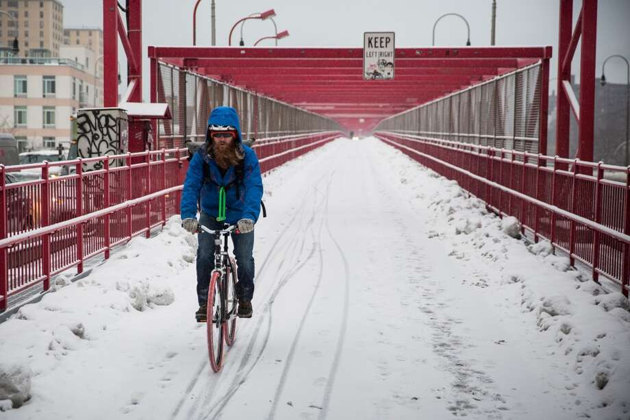 NEW YORK, NY - FEBRUARY 18:  A man rides his bike across the Williamsburg Bridge through snowfall on February 18, 2014 in New York City. The city was hit with its 22nd day of snowfall, making for a total of 48 inches for the year.  (Photo by Andrew Burton/Getty Images) Photo: Getty Images