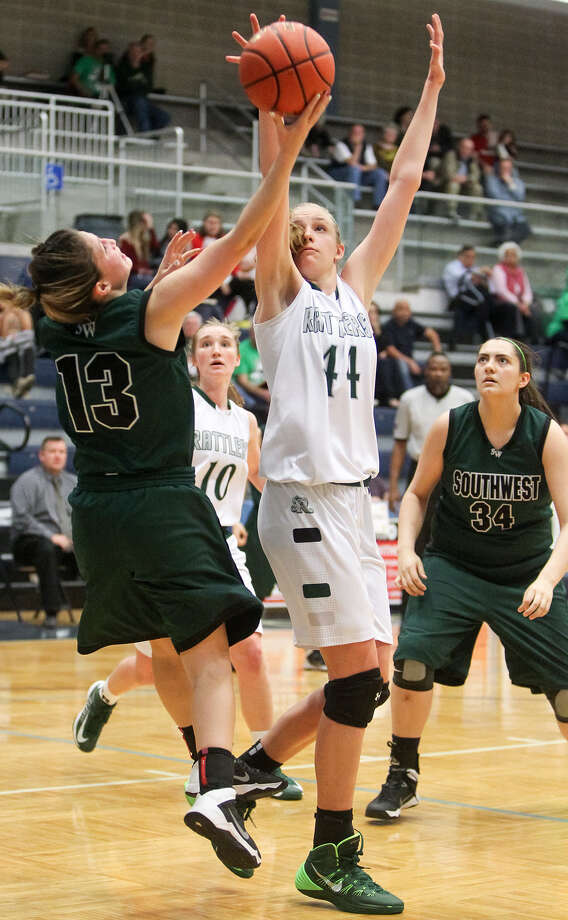 Reagan's Sara Lewis, second from right, blocks a shot by Southwest's Tiffani Rodriguez during their Class 5A playoff game at the Durbon Athletic Center on Friday. Reagan beat the Lady Dragons 78-48. Photo: Marvin Pfeiffer / Stone Oak Weekly / Express-News 2014