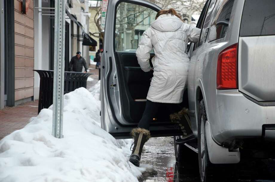 The fresh dusting of snow Tuesday, plus the melting from snow banks accumulated from earlier storms, made navigating between curb and cars on Main Street a challenge. Photo: Jarret Liotta / Westport News contributed